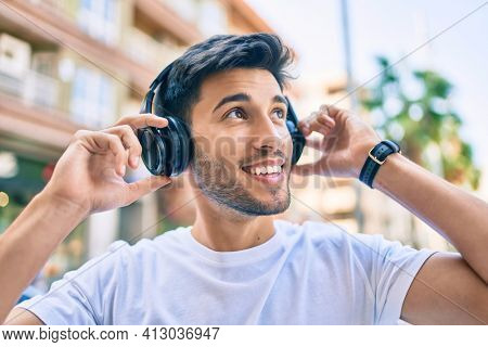 Young latin man smiling happy listening to music using headphones at the city.