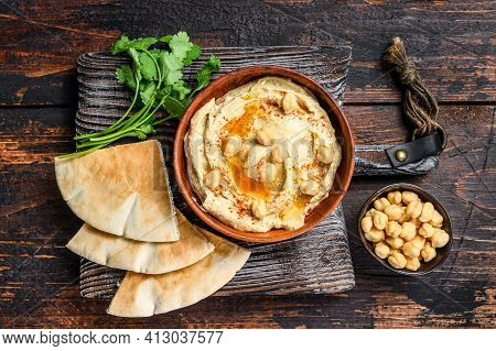 Hummus Paste With Pita Bread, Chickpea And Parsley In A Wooden Bowl. Dark Wooden Background. Top Vie