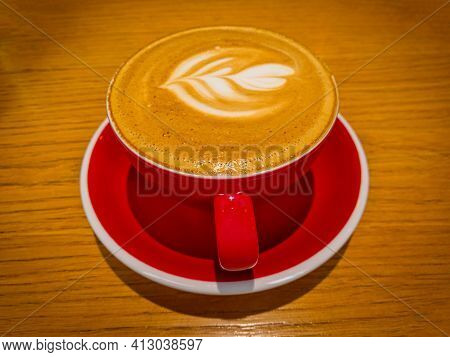 Latte Art On Froth. Hot Latte Coffee On Wooden Table. Morning With A Red Cup Of Cappuccino. Art And