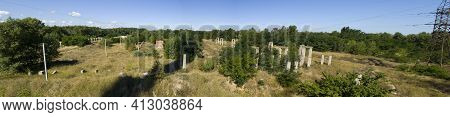 A Panorama Of Piles Of Destroyed Buildings Overgrown With Grass And Trees.