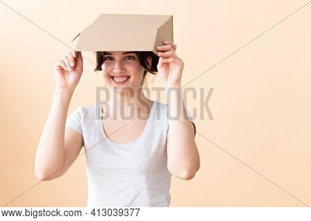 Laughing Girl Holding An Open Cardboard Box Above Her Head, Hiding From The Scorching Sun Or Adverti