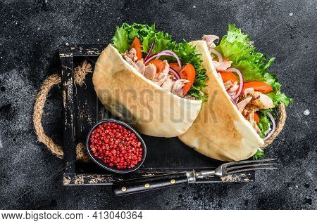Doner Kebab With Grilled Chicken Meat And Vegetables In Pita Bread On A Wooden Tray. Black Backgroun