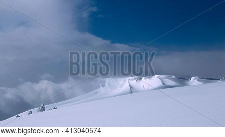 Wind Blows Off The Top Of A Bright White Mountaintop Snow Drift
