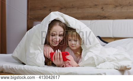 Mother Lying On Bed Under Duvet With Daughter Kid Girl Holding Mobile Phone Watching Online Movies