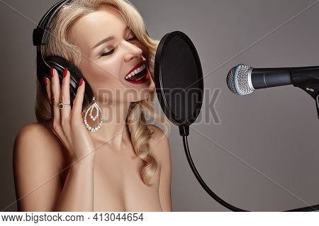 Beautiful Blonde Woman Singing Song In Professional Recording Studio With Microphone, Pop Filter And