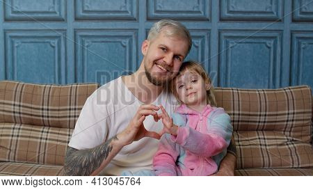 Father And Child Daughter Kid In Pajamas Sit On Couch Smiling, Making Sign Of Shape Heart Near Chest