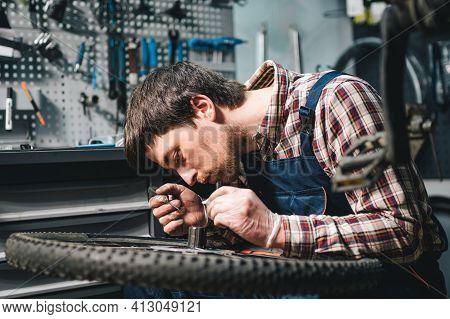 Young Caucasian Repairman Repairing Mountain Bike Wheel In Bike Shop Workshop. Fixing Bicycle. Carin