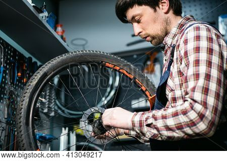 Bicycle Mechanic Fixing Cycle Wheel In Repair Shop. Velocipede Service. Repairer Male Bike Shop Engi