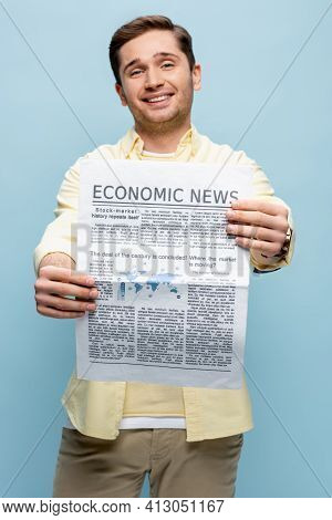 Happy Young Man In Shirt Holding Economical Newspaper Isolated On Blue.