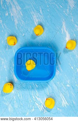 Yellow Rubber Ducks On A Blue Background Close-up. Vertical Photo