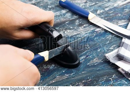 Man Manually Sharpens Kitchen Knives. Knife Sharpening. The Concept Of Caring For Knife Sharpness.