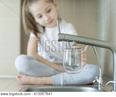 Little Child Is Drinking Fresh And Pure Tap Water From Glass. Water Being Poured Into Glass From Kit