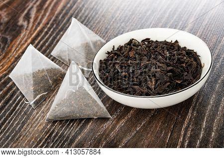 Few Tea Bags With Tea, Leaf Black Tea In White Bowl On Dark Wooden Table