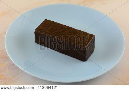 Dark Chocolate Almond Wafer Candy Bar Snack On Small Blue Dessert Plate