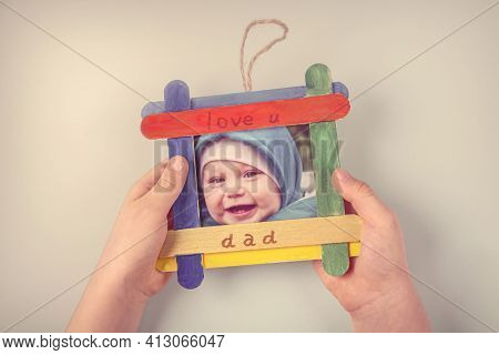Diy And Kid's Creativity. Photo Frame Made From Ice Cream Sticks. Child's Hands Hold Frame. Children