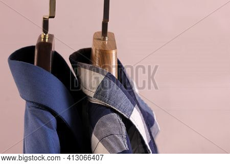 Two Men's Shirts On Plastic Hangers On A Light Background With Copy Space