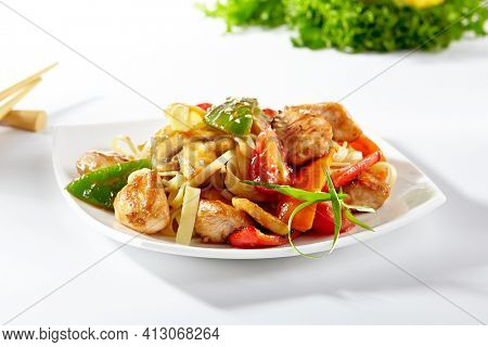Udon noodles with sweet and sour chicken and vegetable. Asian style noodles food on white background. Udon in white plate with wooden choopsticks