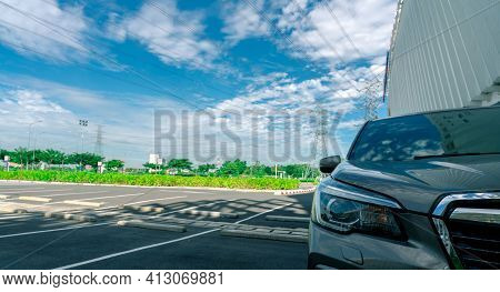 Front View Of Car Parked At Parking Lot. Shopping Mall Outdoor Car Parking Area With Electric Cable