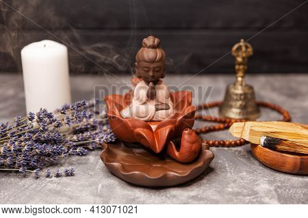 Close Up Of A Buddha Figurine And Smoky Incense With Candle, Bell And Rosary. Aromatherapy. Buddha S