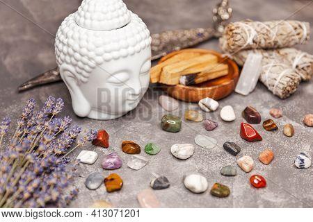 Ceramic Statuette Of A Buddha Head. Selection Of Precious And Semiprecious Stones. White Pillar Cand