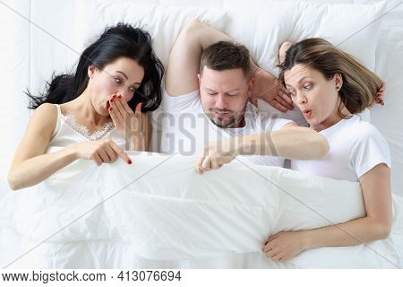 Two Women And One Man Lie On Bed In Bedroom