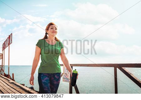Adult Woman In Sportswear With A Shaker In Her Hands, Walking Along The Pier Pier. Copy Space. Outdo