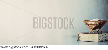Christian Christmas Concept. Birth Of Jesus Christ. Wooden Manger On Holy Bible. Banner, Copy Space.