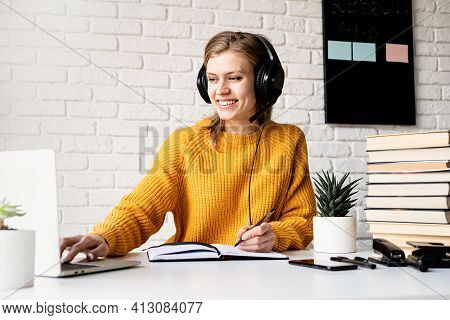 Young Smiling Woman In Black Headphones Studying Online Using Laptop Writing In Notebook
