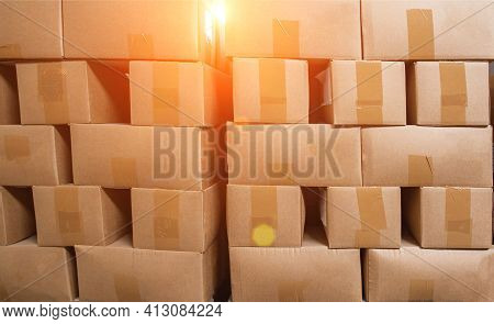 A Pile Of Cardboard Boxes On Pallets Against The Backdrop Of The Sun. The Concept Of Turnover, Produ