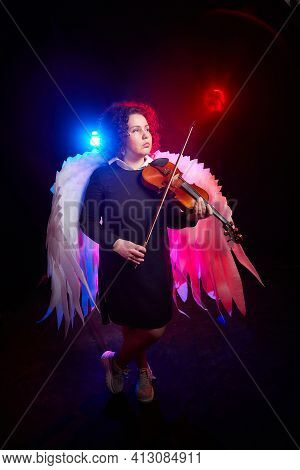 A Brunette Curly Girl In Black Dress Looking As Hipster Or Teenager With Violin And White Angel Wing