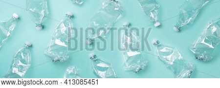 Empty Rumpled Used Plastic Bottle On Blue Background. Top View, Copy Space. Pollution, Environmental