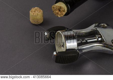 Wine Bottle, Old Corkscrew And Broken Cork On A Gray Background. The Corkscrew Lies Next To A Broken
