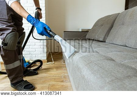 Close Up Man Hand In Protective Rubber Glove Cleaning Sofa With Professionally Extraction Method. Ea