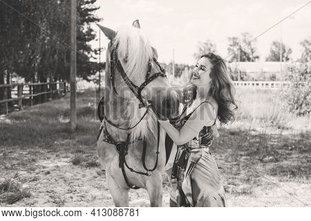 Nice Red Hair Girl At Countryside With A Horse. A Beautiful Rider And Horse. Artistic Photography At
