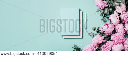 Feminine Workspace With Notebook, Pink Peony, Eucalyptus Flower On Blue Background. Top View, Copy S