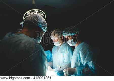 An International Team Of Doctors Performs A Complex Surgical Operation On A Patient Under Anesthesia
