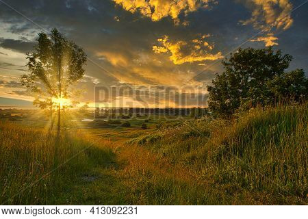 Misty Sunrise Over A River And A Field Of Grass With Path On It