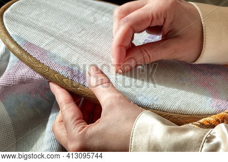 Close Up Woman Hands Doing Needlework On Embroidery Frame. Cross Stitching, Hobby, Diy