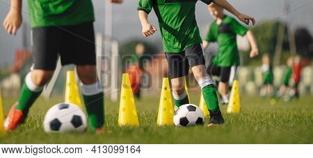 Group Of Football Players On Training Unit. Children Practicing Soccer Skills On Dribbling Trail Of
