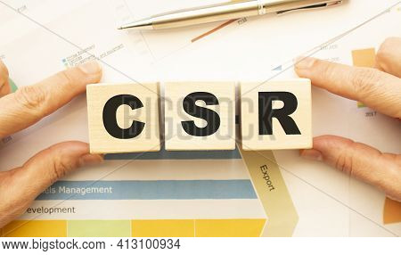 Cropped View Of Hands Holding Wooden Cubes With Csr Lettering On Work Table. Top View