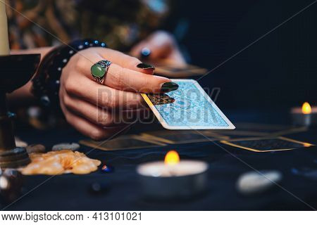 Cartomancy. The Fortune Teller Holds Tarot Card. Close Up. The Concept Of Divination, Astrology And