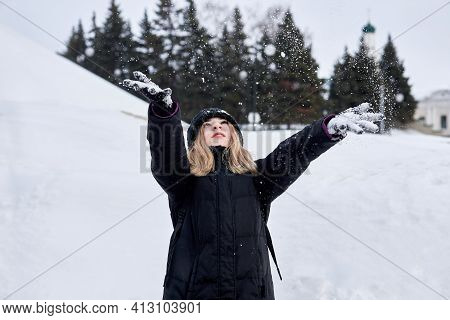 A Young Girl In Black Clothes Catches Falling Snow Flakes. Winter Leisure.