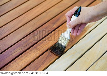 Hand Holding A Brush Applying Varnish Paint On A Wooden Garden Table - Painting And Caring For Wood