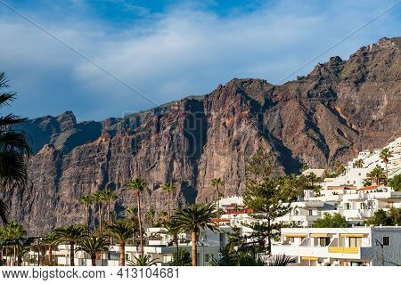 Los Gigantes Village. Palm Trees And White Apartment Houses In Front Of Big Rocks. Holiday Destinati