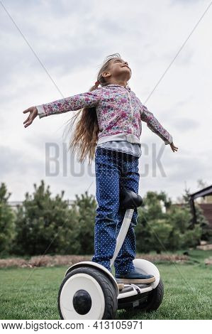 Child Riding On Self-balancing Hover Board On The Backyard Of Cottage, Outdoor Kids Activity