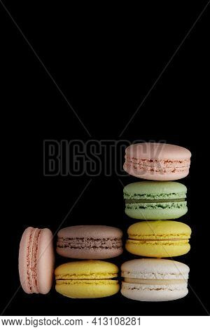 Macaroon. Two Stack Of Colorful Cake Macaron With Pastel Tones And One Macaroon Separately On Black