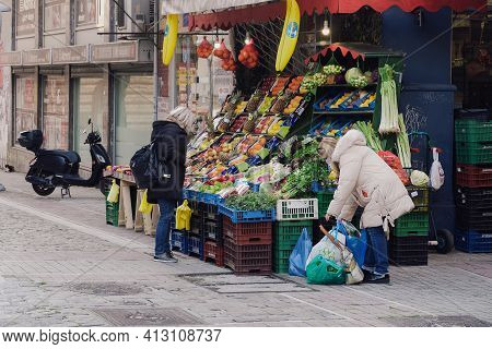 Thessaloniki, Greece - March 13 2021: People Outside Greengrocer Shop With Covid-19 Masks. Food Stor