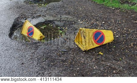 Two Discarded Yellow Traffic Warning Cones Discarded On Rough Ground