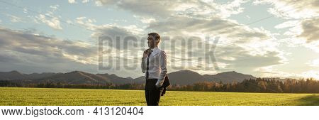 Confident Young Businessman Standing With His Jacket Over The Shoulder In A Beautiful Green Meadow,