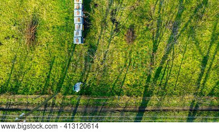 Aerial View On Farmer In Protective Clothing Sprays Fruit Trees In Orchard, Using Long Sprayer To Pr